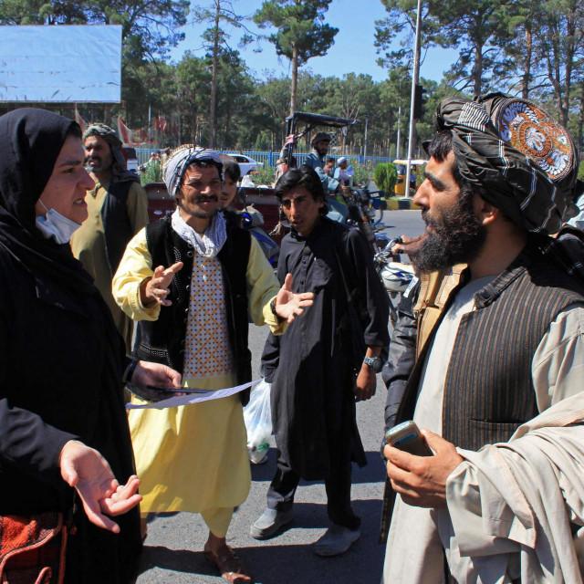 Afganistanska žena razgovara s pripadnikom talibana tijekom prosvjeda