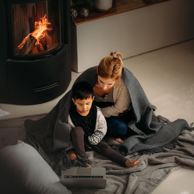 Woman and a little boy with blanket sitting on floor looking at laptop. Mother and son watching cartoons on laptop sitting near fireplace at home.