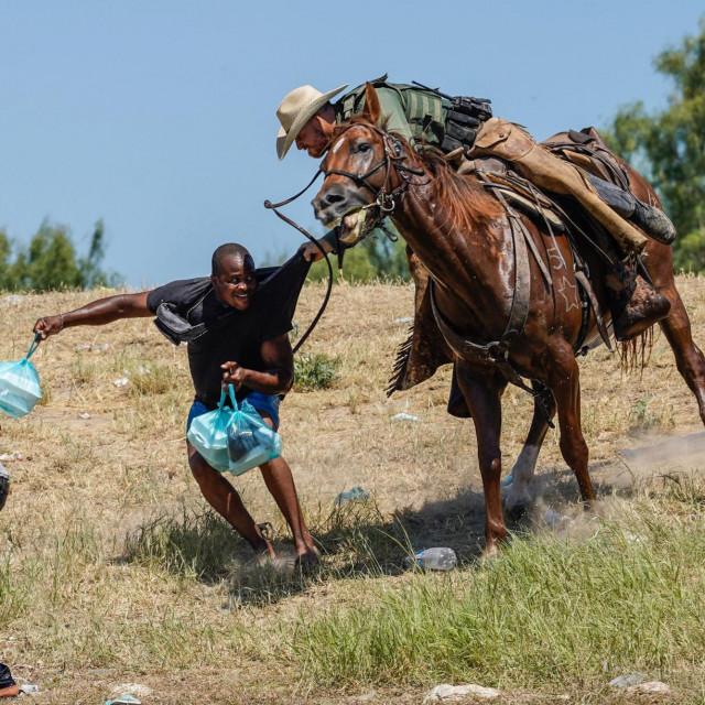 Agent granične ophodnje Sjedinjenih Država na konju pokušava spriječiti migranta iz Haitija da uđe u kamp na obali Rio Grande