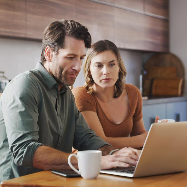Shot of a young couple using a laptop while going over their finances together at home
