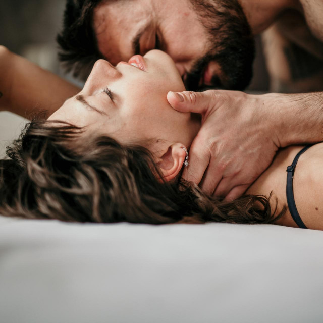 Side view photo of a beautiful couple in bed, being gentle and sensual. Handsome guy with a beard on top of the beautiful brunette is kissing her neck while her eyes are closed. Making love concept