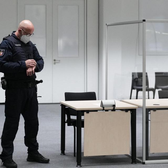 Službenik suda gleda na sat u sudnici prije suđenja 96-godišnjoj bivšoj tajnici