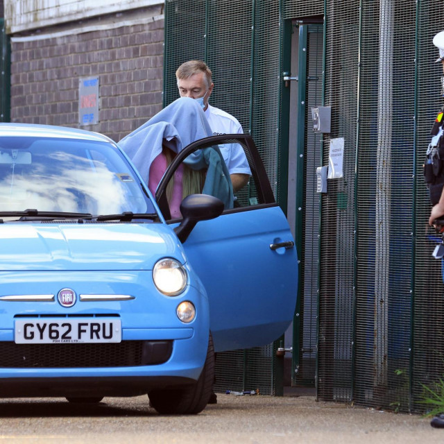 Dok je izlazila iz zgrade suda, Katie se pred novinarima skrivala dekom