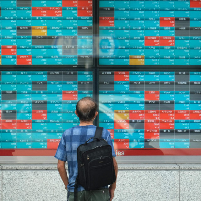 A pedestrian looks at an electronic quotation board displaying compnaies' stock prices of the Tokyo Stock Exchange in Tokyo on October 5, 2021. (Photo by Kazuhiro NOGI/AFP)