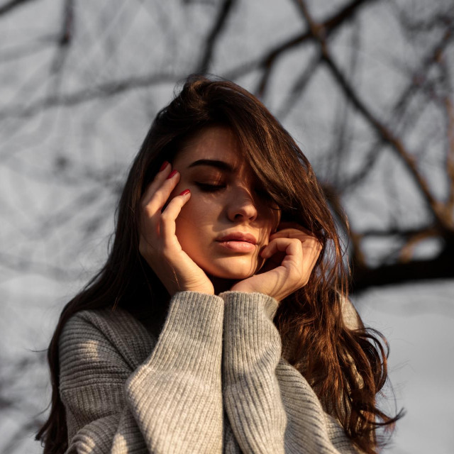 Low angle of young sad female in sweater touching face on blurred background of leafless tree branches in nature