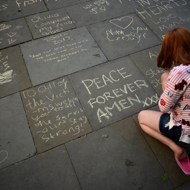 Žena gleda poruke ispisane na pločniku u centru Manchestera 22. svibnja 2018., na obljetnicu godine dana od smrtonosnog napada na Manchester Arenu