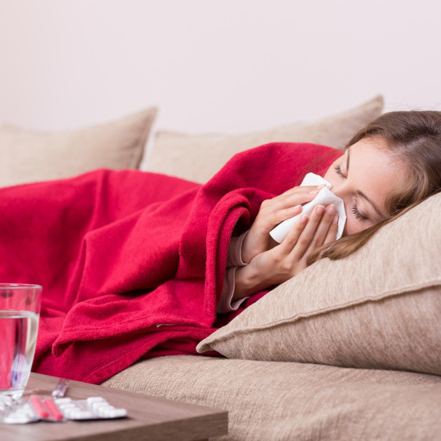 Sick woman covered with a blanket lying in bed with high fever and a flu, blowing her nose. Pills and glass of water on the table